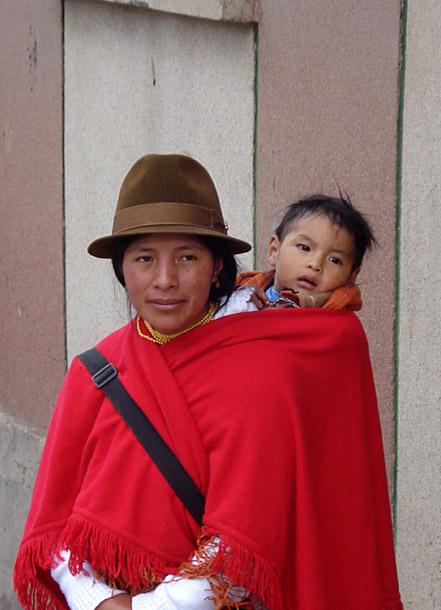 Ecuadorianische Mutter mit Kind. Die Kinder werden in Tüchern auf dem Rücken getragen und überallhin mitgenommen.