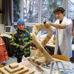 Zwei interessierte Sechstklässler beobachten Pascal aus dem LK Kunst der 13. bei der Arbeit an seiner Skulptur.